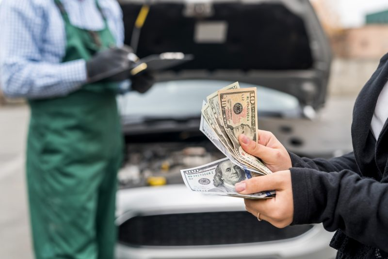 Female hands with dollars, payment for car service